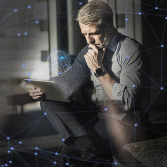 Mature businessman using tablet surrounded by virtual globe and lines - UUF17921