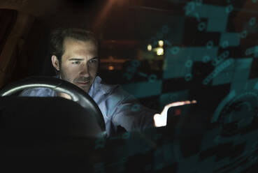 Businessman using device in car at night surrounded by data - UUF17924