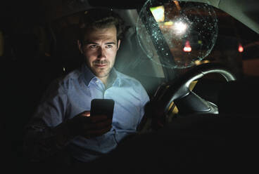 Businessman using smartphone in car at night surrounded by virtual shining globe - UUF17927