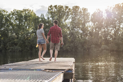 Young couple walking hand in hand on jetty at a remote lake - UUF17933