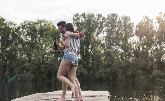 Happy young couple having a drink and embracing on jetty at a remote lake - UUF17936
