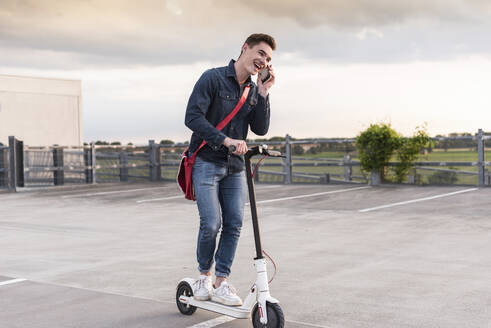 Happy young man with cell phone and electric scooter on parking deck - UUF17954