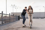 Young man and woman riding on longboard and electric scooter on parking deck - UUF17966