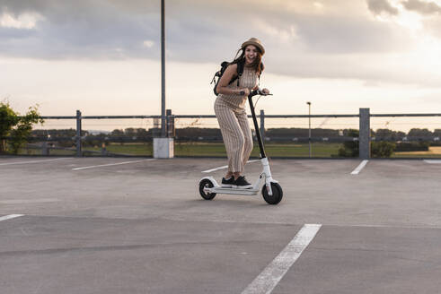 Happy young woman on electric scooter on parking deck - UUF17969