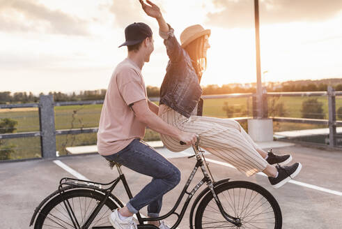 Happy young couple together on a bicycle on parking deck at sunset - UUF17972