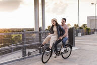 Happy young couple together on a bicycle on parking deck at sunset - UUF17975