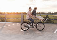 Happy young couple together on a bicycle on parking deck at sunset - UUF17978