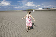 Back view of little girl running on the beach, Bergen op Zoom, Netherlands - KMKF00985
