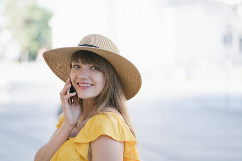 Portrait of beautiful woman talking over smart phone while standing in city - AHSF00580