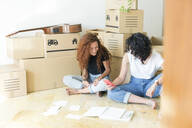 Two friends moving into new home using cell phone - JPTF00222