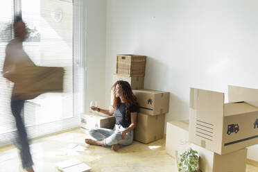 Young woman sitting in new home with glass of red wine while friend is moving fast with cardboard box - JPTF00225