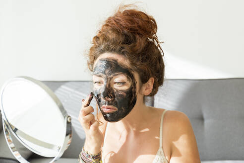 Young woman applying facial mask at home - JPTF00234