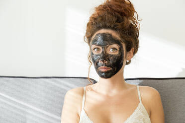 Portrait of young woman wearing facial mask at home - JPTF00237