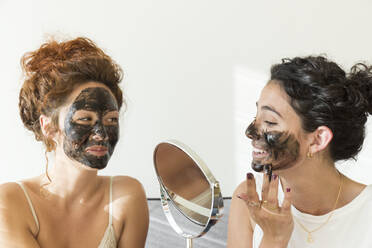 Two happy young women applying facial masks at home - JPTF00240