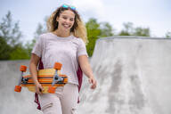 Smiling young woman with a longboard at a skatepark - STSF02047