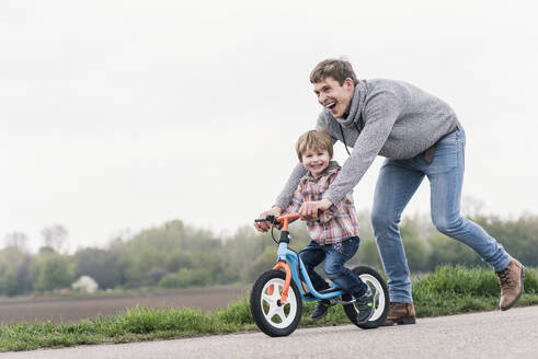 Father teaching his son how to ride a bicycle, outdoors - UUF17991