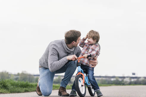Father teaching his son how to ride a bicycle, outdoors - UUF17994