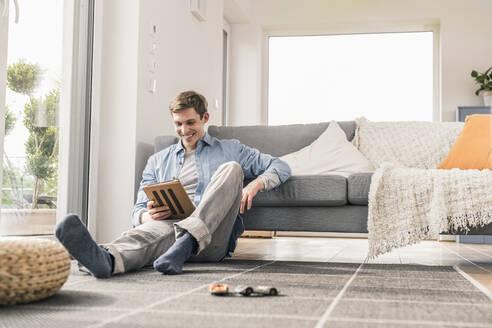 Mid adult man sitting on floor, using digital tablet - UUF18012