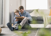Father and son sitting on floor, using digital tablet - UUF18015