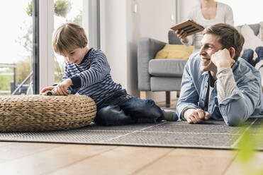 Father and son playing with toy cars, lying on floor - UUF18018