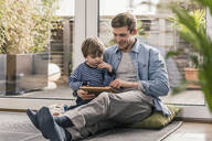 Father and son sitting on floor, using digital tablet - UUF18027