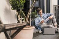 Man sitting on terrace, using laptop - UUF18036