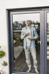 Man standing by glass door, drinking coffee, smiling - UUF18039