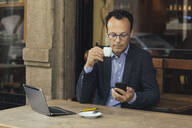 Businessman with laptop in a coffee shop looking at his smartphone - ALBF00887