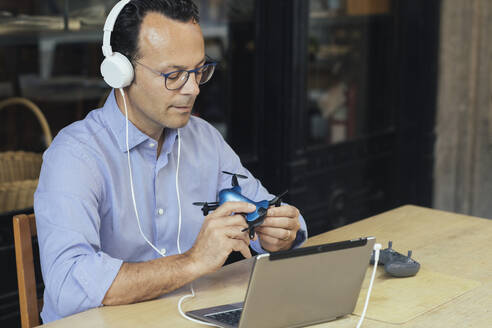 Businessman with headphones, laptop and drone in a coffee shop - ALBF00890