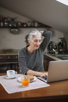 Portrait of senior woman using laptop at breakfast table - ALBF00896