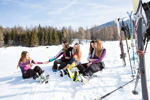 Five teenage girl skiers sitting in snow covered landscape, Tyrol, Styria, Austria - CUF51630