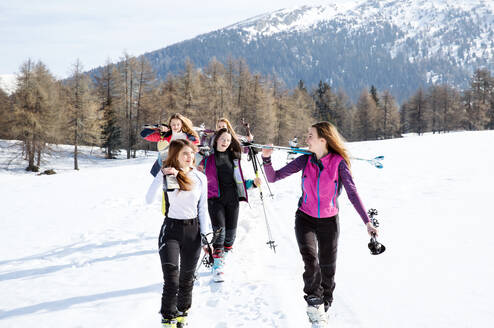 Five teenage girl skiers walking in snow covered landscape, Tyrol, Styria, Austria - CUF51633