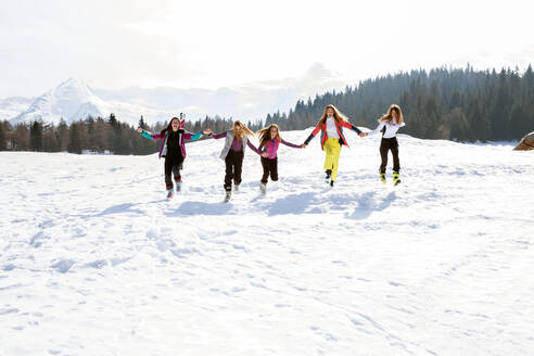 Five teenage girl skiers running and laughing in snow covered landscape, Tyrol, Styria, Austria - CUF51648