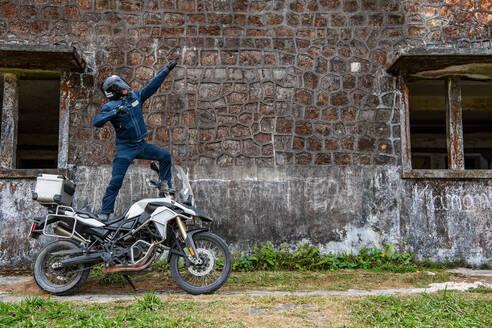 Biker posing in superhero gesture on ADV motorbike, Phnom Penh, Cambodia - CUF51666