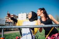 Calisthenics class at outdoor gym, two young women taking smartphone selfie - CUF51681