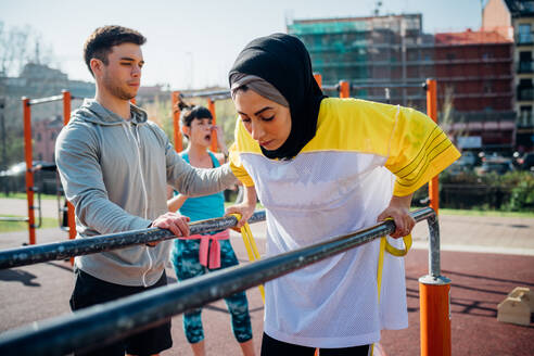 Calisthenics class at outdoor gym, male trainer encouraging young woman on parallel bars - CUF51702