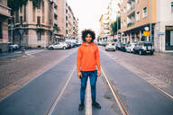Young man in middle of city street, Milano, Lombardia, Italy - CUF51831