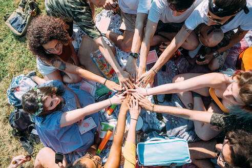 Group of friends overlapping hands in circle in park - CUF51876