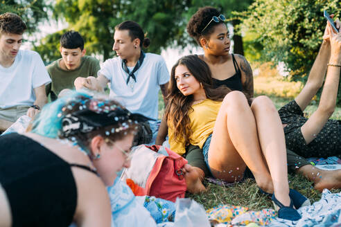 Group of friends relaxing at picnic in park - CUF51897