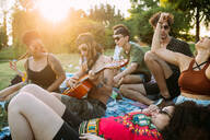 Group of friends relaxing, playing guitar at picnic in park - CUF51909