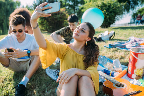 Group of friends relaxing, taking selfie at picnic in park - CUF51912