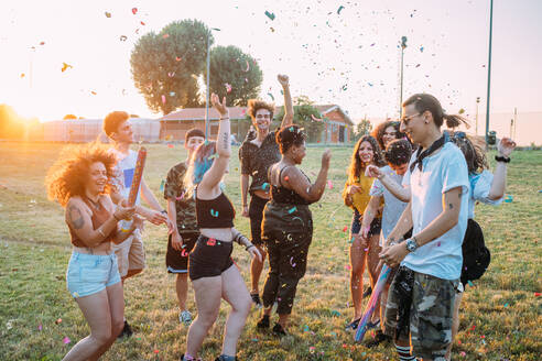 Group of friends dancing, playing with confetti in park - CUF51915