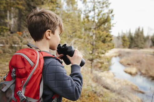 Boy with backpack using binoculars, hiking in woods - HEROF36777