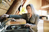 Woman filling pot with water, cooking in cabin kitchen - HEROF36789