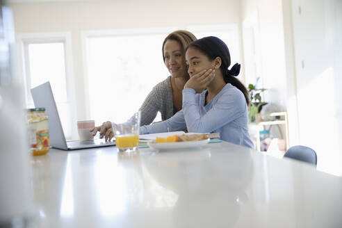 Mother helping daughter with homework at laptop in kitchen - HEROF36810