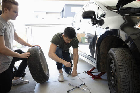 Young men changing car tire in garage - HEROF36831