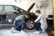 Young men changing car tire in garage - HEROF36834