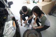 Mother and son with digital tablet learning to change car tire in garage - HEROF36846