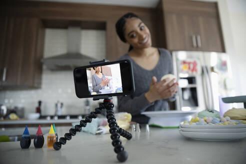 Teenage girl vlogging, decorating cupcakes in kitchen - HEROF36885