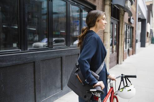 Businesswoman with bicycle on urban sidewalk - HEROF36909